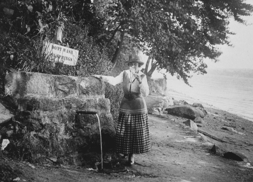 A woman drinks from a park spring